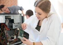 Ragazza degli studenti che ripara computer Fotografie Stock