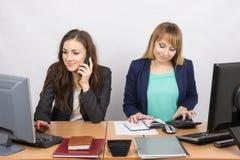 Ragazza dei colleghi di ufficio che si siede dietro uno scrittorio, con un telefono, l'altro con un calcolatore Immagini Stock Libere da Diritti