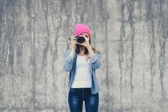 Ragazza dei pantaloni a vita bassa in abbigliamento dei jeans e cappello rosa che prendono foto contro il muro di cemento grigio  fotografie stock libere da diritti