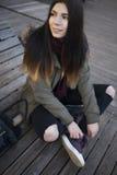 Ragazza dei pantaloni a vita bassa in cappotto del parka che si siede all'aperto Fotografia Stock