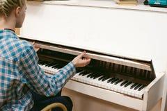 Ragazza dei pantaloni a vita bassa che gioca piano bianco d'annata Fotografia Stock