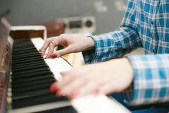 Ragazza dei pantaloni a vita bassa che gioca piano bianco d'annata Fotografie Stock