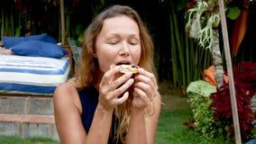 Ragazza dei pantaloni a vita bassa che mangia pizza e che sorride alla macchina fotografica nel ristorante stock footage