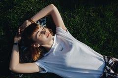 Ragazza dei pantaloni a vita bassa che si rilassa sull'erba Immagini Stock