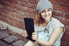 Ragazza dei pantaloni a vita bassa che si siede con un computer portatile Immagine Stock