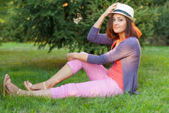Ragazza dei pantaloni a vita bassa che si siede sull'erba verde Fotografia Stock