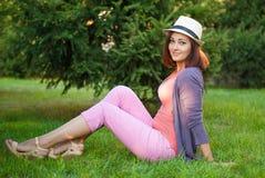 Ragazza dei pantaloni a vita bassa che si siede sull'erba verde Fotografie Stock Libere da Diritti
