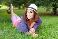 Ragazza dei pantaloni a vita bassa che si trova nell'erba verde Immagini Stock