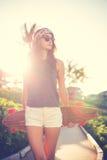 Ragazza dei pantaloni a vita bassa con gli occhiali da sole d'uso del bordo del pattino Immagini Stock Libere da Diritti