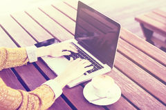 Ragazza dei pantaloni a vita bassa con il computer portatile, la tazza di caffè e lo smartphone all'aperto Fotografie Stock