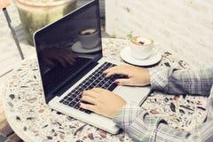 Ragazza dei pantaloni a vita bassa con il computer portatile, tazza di caffè sulla tavola all'aperto Fotografia Stock