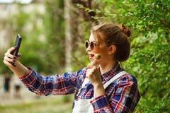 Ragazza dei pantaloni a vita bassa con il selfie della lecca-lecca e del telefono cellulare Fotografia Stock