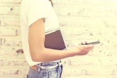 Ragazza dei pantaloni a vita bassa con il telefono cellulare ed i libri Fotografia Stock Libera da Diritti