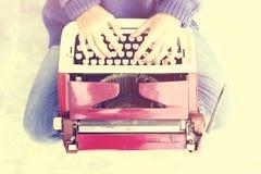 Ragazza dei pantaloni a vita bassa con la macchina da scrivere di vecchio stile Fotografia Stock