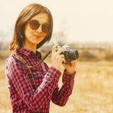 Ragazza dei pantaloni a vita bassa con la vecchia macchina fotografica della foto in primavera all'aperto Fotografie Stock