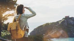 Ragazza dei pantaloni a vita bassa con lo zaino che gode del tramonto su vista sul mare sulla montagna di punta Viaggiatore turis immagine stock