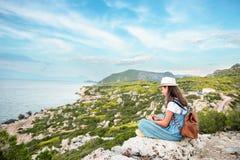 Ragazza dei pantaloni a vita bassa con lo zaino luminoso che gode del mare panoramico della montagna, facendo uso della mappa e g immagini stock