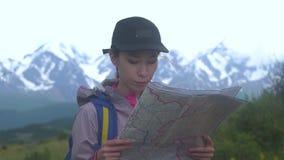 Ragazza dei pantaloni a vita bassa con lo zaino sul picco della montagna che guarda mappa Viaggiatore turistico sulla vista del p video d archivio
