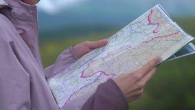 Ragazza dei pantaloni a vita bassa con lo zaino sul picco della montagna che guarda mappa Viaggiatore turistico sulla vista del p archivi video