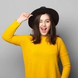 Ragazza dei pantaloni a vita bassa con sbattere le palpebre del cappello Fotografie Stock