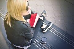 Ragazza dei pantaloni a vita bassa con un libro rosso Fotografie Stock Libere da Diritti