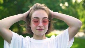 Ragazza dei pantaloni a vita bassa in occhiali da sole rosa che decolla elastico e che gioca con i suoi capelli archivi video