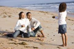 Ragazza del African-American con i genitori sulla spiaggia Fotografie Stock Libere da Diritti