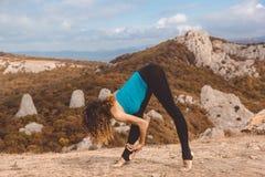 Ragazza del ballerino nel paesaggio delle montagne che fa allungamento Fotografia Stock
