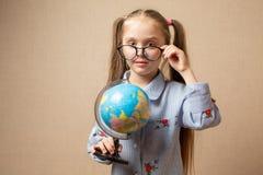 Ragazza del bambino abbastanza piccolo in vetri con il globo Fotografia Stock