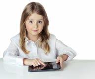 Ragazza del bambino al computer portatile della compressa della tenuta della tavola isolato Immagine Stock Libera da Diritti