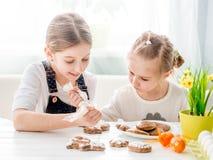 Ragazza del bambino che decora i biscotti di Pasqua Fotografia Stock Libera da Diritti