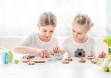 Ragazza del bambino che decora i biscotti di Pasqua fotografia stock