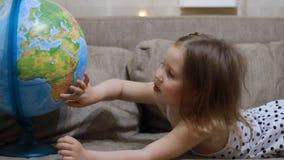 Ragazza del bambino che gioca con il globo Il bambino studia la geografia e una mappa del mondo stock footage
