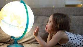 Ragazza del bambino che gioca con il globo Il bambino studia la geografia e una mappa del mondo archivi video