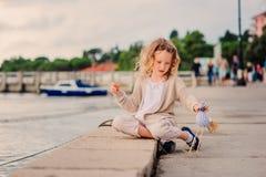 Ragazza del bambino che gioca con l'uccello del giocattolo sulla spiaggia sulle vacanze estive con il fondo del mare Immagini Stock Libere da Diritti
