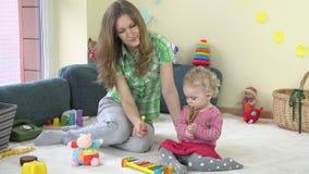 Ragazza del bambino che gioca gli strumenti come il metallophone ed il crepitio con la babysitter video d archivio