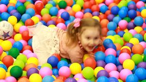 Ragazza del bambino che gioca sul campo da giuoco con i palloni variopinti Giochi del bambino nella stanza per i giochi archivi video