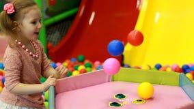 Ragazza del bambino che gioca sul campo da giuoco con i palloni variopinti Giochi del bambino nella stanza per i giochi stock footage