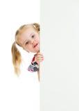 Ragazza del bambino che guarda dal manifesto in bianco dell'insegna immagine stock