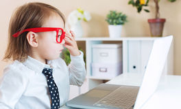 Ragazza del bambino che indossa i grandi vetri rossi mentre per mezzo del suo computer portatile Fotografie Stock Libere da Diritti