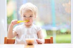 Ragazza del bambino che mangia il purè della frutta Immagini Stock