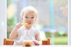 Ragazza del bambino che mangia il purè della frutta Immagini Stock Libere da Diritti