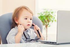 Ragazza del bambino che mette sui grandi vetri mentre per mezzo del suo computer portatile Fotografia Stock Libera da Diritti