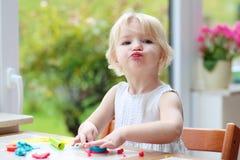 Ragazza del bambino che produce i biscotti dal plasticine fotografie stock libere da diritti