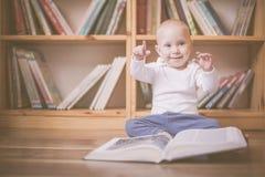 Ragazza del bambino che si siede con i libri davanti agli scaffali di libro Fotografie Stock