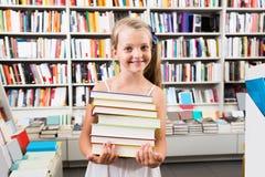 Ragazza del bambino che tiene una pila di libri in una libreria Fotografie Stock Libere da Diritti