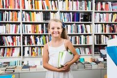 Ragazza del bambino che tiene una pila di libri in una libreria Immagine Stock Libera da Diritti