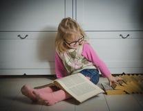 Ragazza del bambino con i vetri e una pila di libri che si siedono sul pavimento, Fotografia Stock