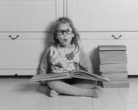 Ragazza del bambino con i vetri e una pila di libri che si siedono sul pavimento, in bianco e nero Immagine Stock