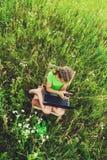 Ragazza del bambino con il computer portatile ed il telefono in natura fotografia stock